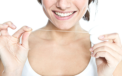Woman smiling with dental floss in hand