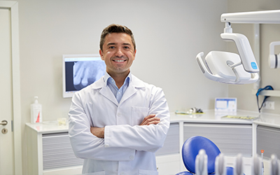 A male dentist standing in a dentist office smiling