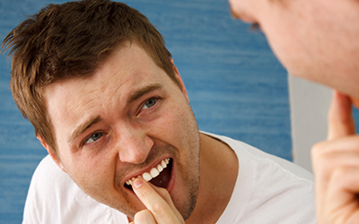 Man looking at a tooth in the mirror