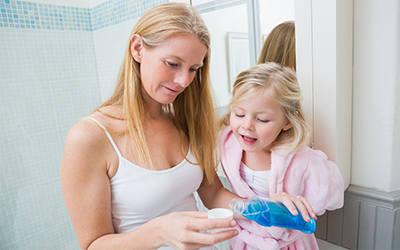 A woman with a young child pouring mouthwash into a cup