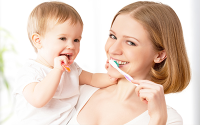 A mother and baby brushing their teeth